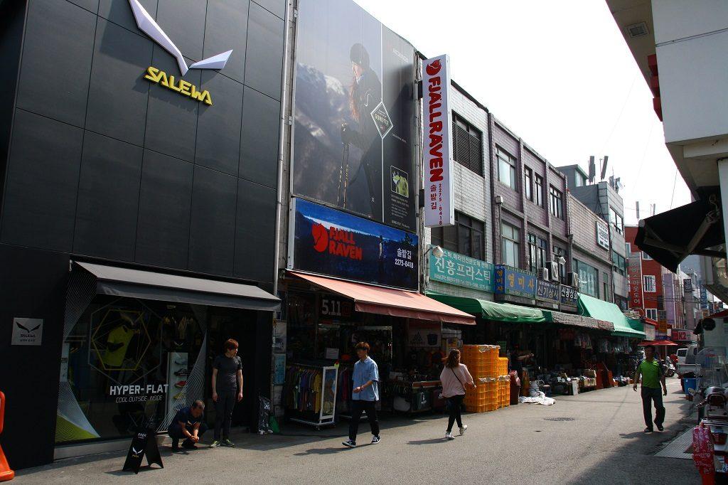 Firmowy sklep Fjallravena naprzeciw sklepików z drutami i budki z kimchi